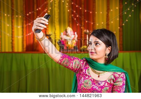 indian attractive girl taking selfie picture on cel phone or mobile phone or smartphone in ganpati festival or ganesh utsav