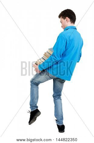 A man carries a heavy pile of books. back view. curly-haired student in a blue sweater is trying to keep warm textbooks.