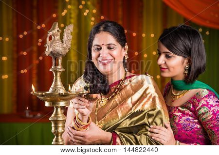 Indian young girl in traditional wear and mother in saree lighting oil lamp or samai with diya and celebrating ganesh festival or Diwali or deepavali. Indian lady hands holding oil lamp indoors.