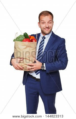 Handsome young businessman in suit holds shopping bag full of groceries and winks, isolated at white background. Healthy food shopping. Paper package with vegetables and fruits, happy male buyer.
