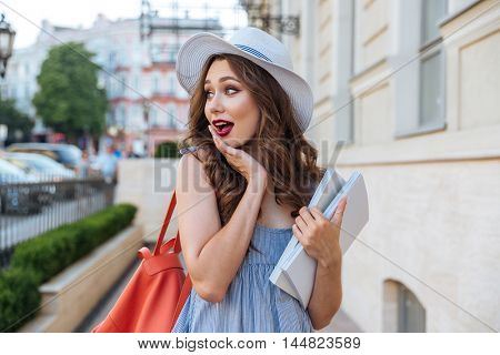 Amazed charming young woman with backpack and blank books walking on the street