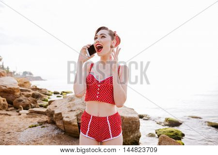 Happy laughing pretty pin up girl in red swimsuit talking on the phone while standing at the beach