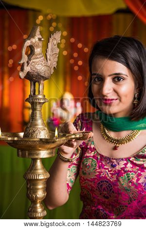 Indian young and beautiful girl in traditional wear lighting oil lamp or samai with diya and celebrating ganesh festival or Diwali or deepavali. Indian girl hands holding oil lamp indoors.