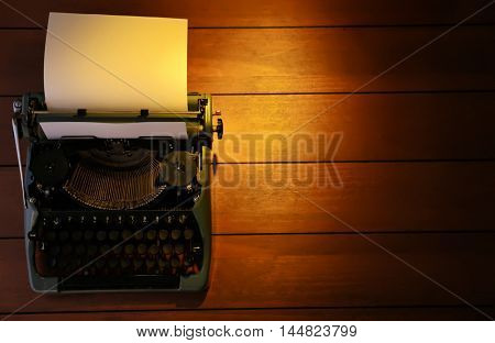 Typewriter on wooden background, top view