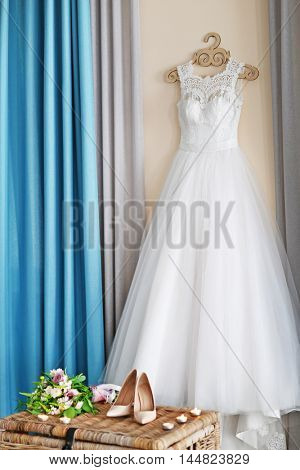 Shoes on wicker chest and wedding dress hanging on wall in room