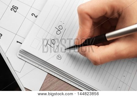 Female hand writing to do list in notebook, closeup