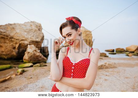Young beautiful lovely pin up girl in red swimsuit posing while standing at the beach