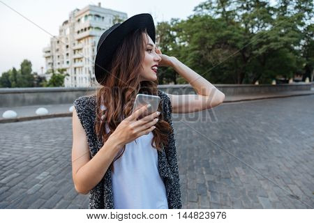 Young beautiful stylish brunette girl using her smartphone outdoors