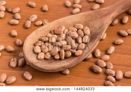 Carioca Beans into a spoon over a wooden table