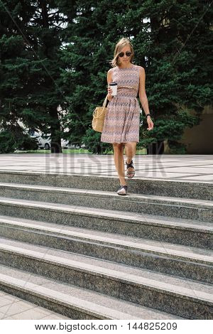Portrait of young brunette woman in dress and sunglasses walking down the steps with coffee to go against the green trees