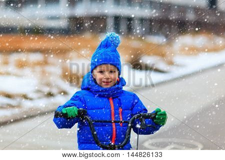 happy cute little boy riding bike in winter, kids sport
