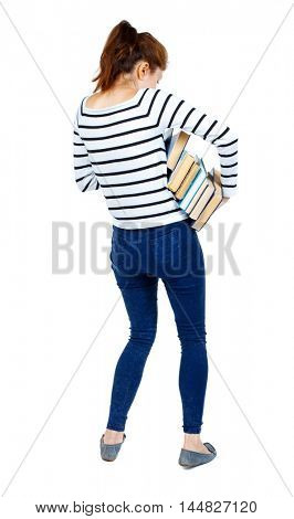 Girl carries a heavy pile of books. Girl in a striped sweater tries to hold a big stack of books in her hands.