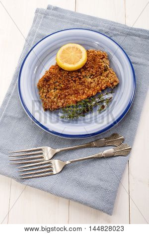 scottish with oatmeal coated kipper with thyme and slice lemon an a blue plate