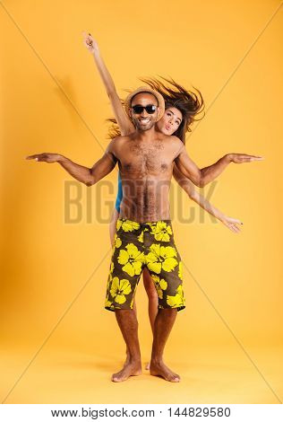 Loving smiling couple in swimwear having fun isolated on the orange background