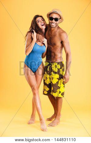 Loving smiling couple in swimwear isolated on the orange background