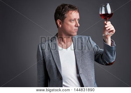 A middle age man holding up and looking through a glass of wine