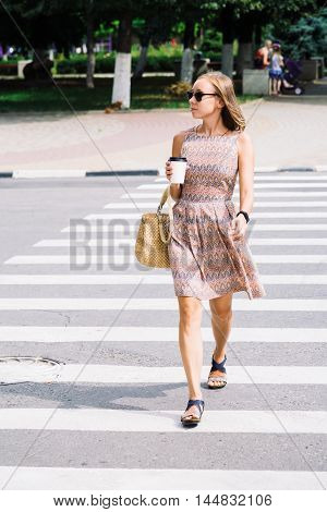 Portrait of young woman in dress and sunglasses walking along zebra crossing with coffee and looking away