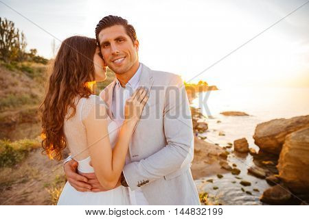 Cheerful married couple standing on the beach at sunset