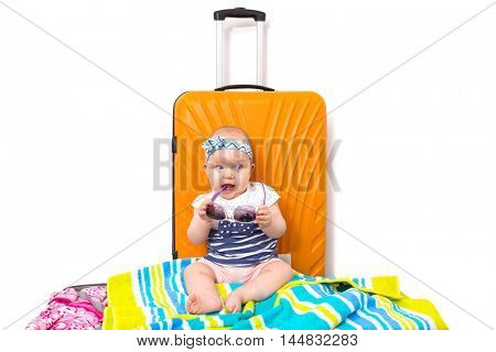 Baby girl packed for travel on the luggage bag