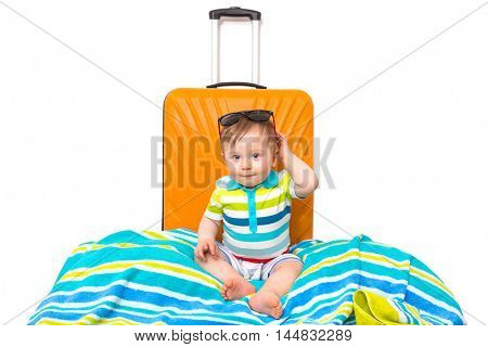 Baby boy packed for travel on the luggage bag