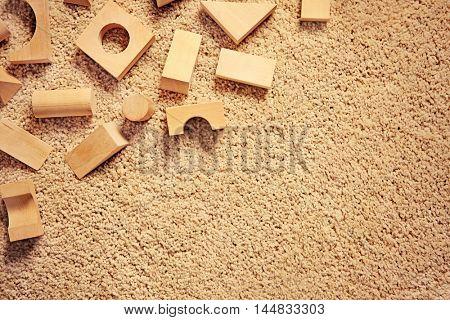 Children's wooden building blocks on carpet, top view
