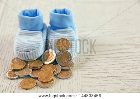 Parenting expenses concept. Baby booties and pile of coins