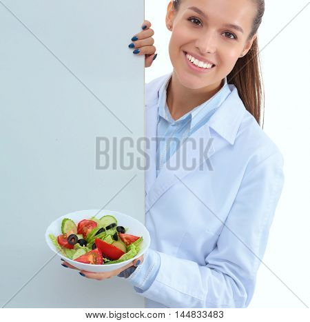 Portrait of a beautiful woman doctor holding a plate with fresh vegetables standing near blank