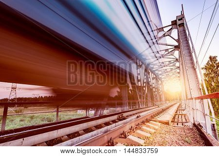 Highspeed train moves fast on the bridge at sunsset.
