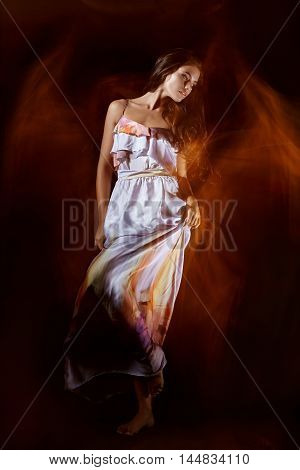 An attractive girl in a bright dress with bright halos around in dark background mixed light.