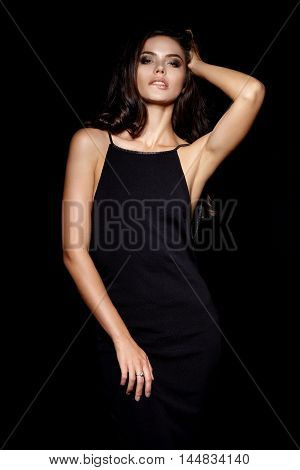 Beautiful young girl in black dress on a black background.