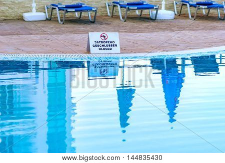 a sparkling pool enclosed with the sign no swimming