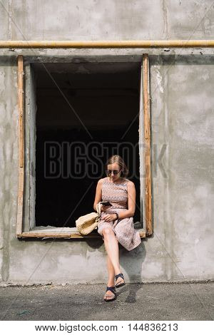 Portrait of adult woman in dress and sunglasses using phone while sitting on window of unfinished building