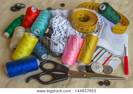 Sewing accessories. Spools of different color thread scissors buttons measuring tape and accessories for needlework.