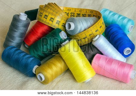 Sewing accessories. Coils of threads of different colors measuring tape on light background.