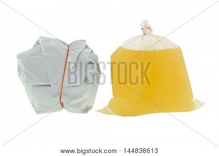 Takeout Thai Food wrapped in white paper package with red rubber band and hot clear soup for takeaway, isolated on white background
