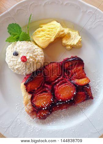 Austrian Plum sheet Cake called Zwetschkenfleck with Vanilla icecream and whipped cream, traditional dessert in Vienna, Austria