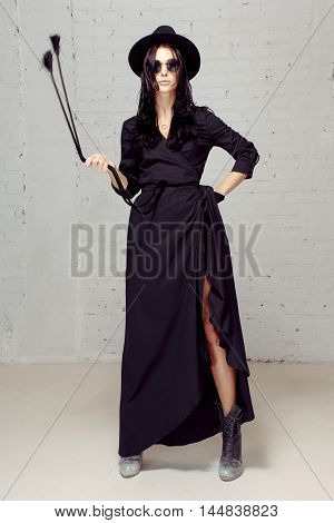 Model in studio in black clothes near brick wall holding in her hand a cord with a brush, imagining like she is witch