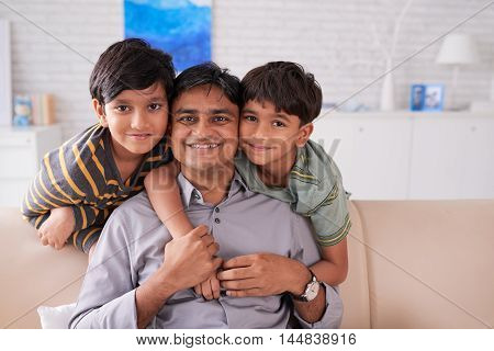 Happy Indian family of three looking at camera