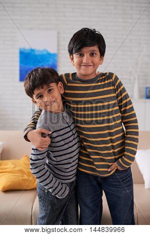 Portrait of two hugging Indian brothers looking at camera