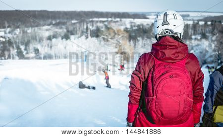 girl in ski suit  on a snowhill view from back