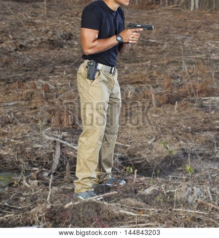 Man with his handgun out of the holster and held in front