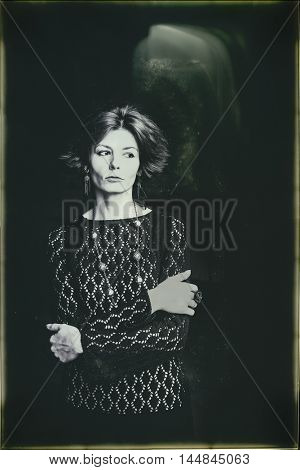 Black and white portrait of young sad woman. Artistic film grain and dust for dramatic effect