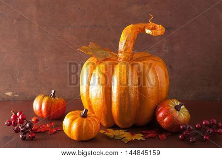 decorative golden papier-mache pumpkin and autumn leaves for halloween thanksgiving