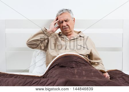 Senior man can not sleep. He is lying in his bed with headache.