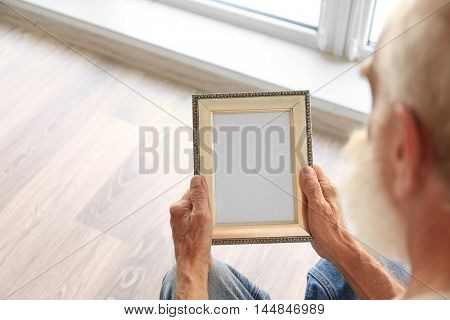 Old man holding photo frame