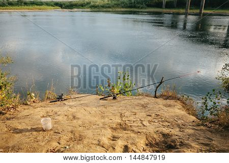 fishing rod standing by the river .  send .