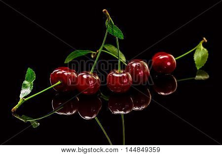 Transparent cup with red ripe cherries with reflection on black background.