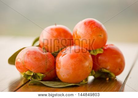ripe persimmons on a table, outdoor