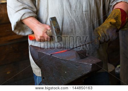 Leningrad region, Podporozhsky District, Russia - June 26 2016: Blacksmith working in his shop using an anvil - The village of Upper Mandrogi is a reproduction of a traditional Russian village.