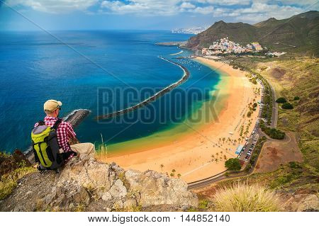 tourist man sitting on the edge of a cliff enjoying amazing sea view of the beach Playa de Las Teresitas in Tenerife Canary Islands Spain